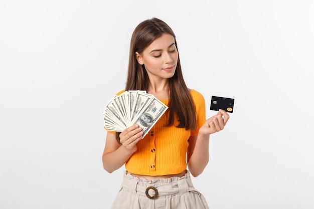 Mulher bonita com blusa laranja, segurando as notas e cartão de crédito