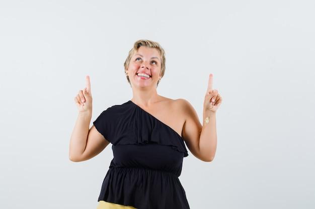 Mulher bonita com blusa preta apontando para cima e parecendo divertida