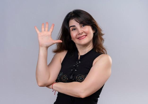 Mulher bonita com blusa preta e feliz mostrando cinco com a mão