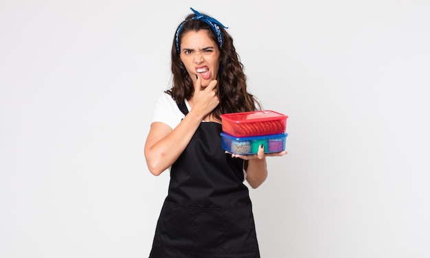 Mulher bonita com boca e olhos bem abertos e mão no queixo segurando tupperwares com comida