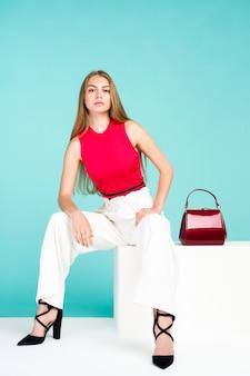 Mulher bonita com bolsa bolsa de mão com sapatos de salto alto sentada no banco branco - imagem