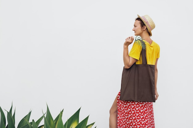 Mulher bonita com bolsa reutilizável de algodão estilo minimalista jovem contra a parede branca
