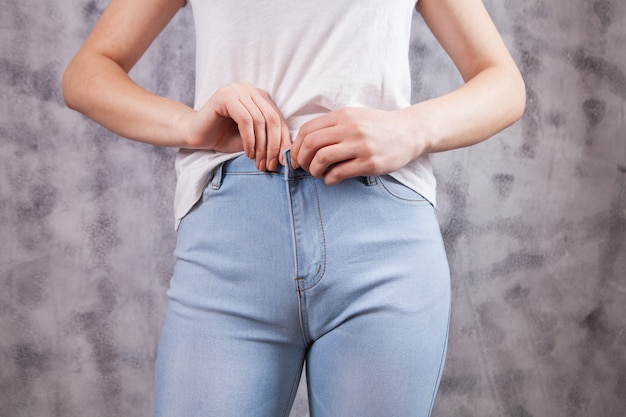 Mulher bonita com botões na calça jeans
