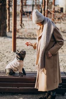 Mulher bonita com buldogue francês andando no parque