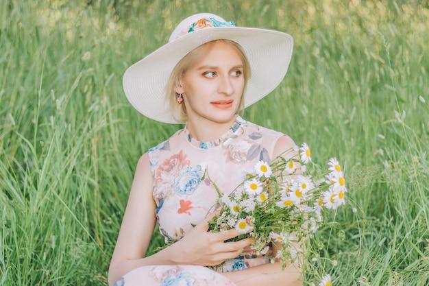 Mulher bonita com buquê de margaridas no fundo da grama alta na temporada de verão.