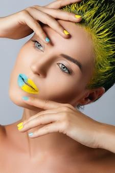 Mulher bonita com cabelo amarelo e unhas e lábios coloridos