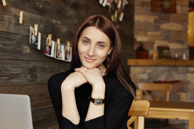 Mulher bonita com cabelo castanho e um lindo sorriso olhando para a câmera enquanto relaxa em um café aconchegante