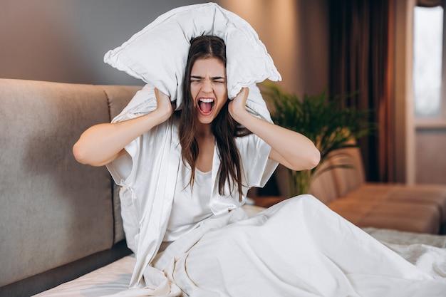 Mulher bonita com cabelo castanho grita enquanto está sentada na cama. mulher jovem cobre os ouvidos com um travesseiro. dor de cabeça por barulho.