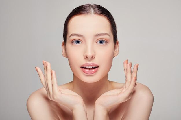 Mulher bonita com cabelo castanho, ombros nus de pele fresca limpa, segurando a mão perto do rosto