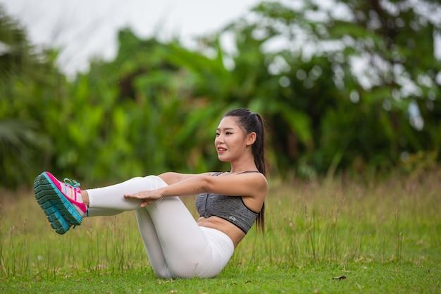 Mulher bonita com cabelo comprido, exercitando-se no gramado do parque.
