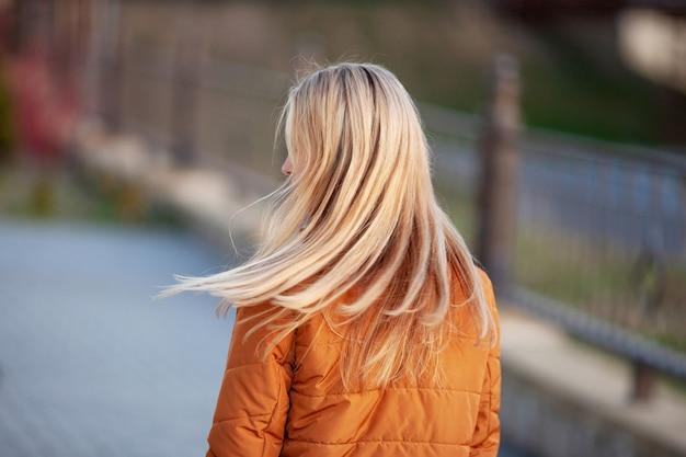 Mulher bonita com cabelo comprido na rua ao pôr do sol