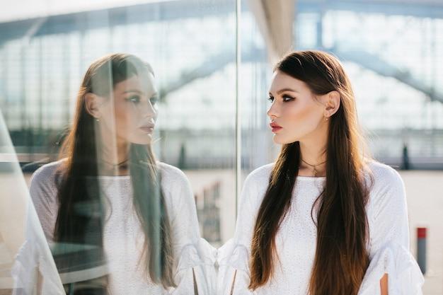 Mulher bonita com cabelo comprido olha para seu reflexo no moderno edifício de vidro