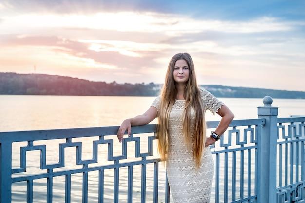 Mulher bonita com cabelo comprido posando contra o pôr do sol