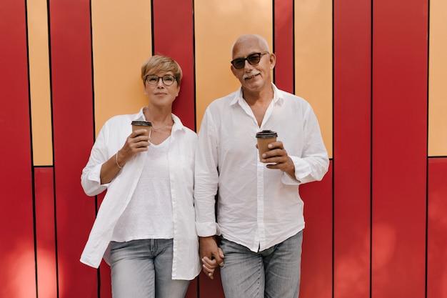 Mulher bonita com cabelo curto com roupas leves, posando com uma xícara de café e segurando a mão com um homem de cabelos grisalhos em vermelho e laranja.