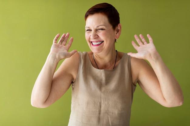 Mulher bonita com cabelo curto, levantando as mãos