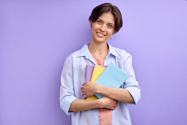 Mulher bonita com cabelo curto, segurando livros nas mãos, sorrindo para a câmera, vestindo roupa casual. aprendizagem, estudo, educação, conceito de universidade