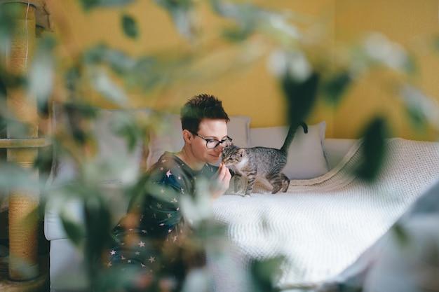 Mulher bonita com cabelo curto senta-se perto do sofá com seu gato adorável atrás de uma flor