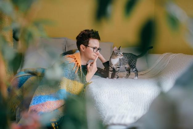 Mulher bonita com cabelo curto, senta-se perto do sofá com seu gato adorável