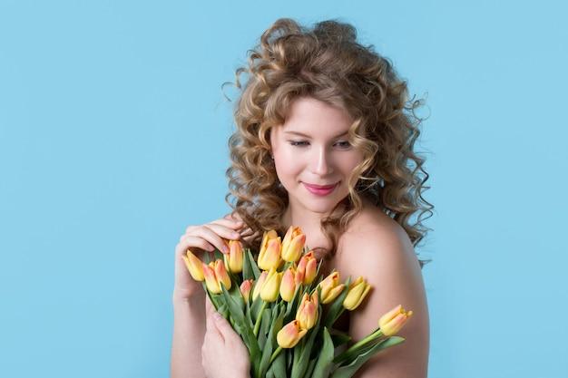 Mulher bonita com cabelo encaracolado com um buquê de flores sobre fundo azul.