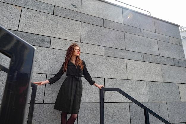 Mulher bonita com cabelo encaracolado nas roupas pretas de pé contra a parede de pedra