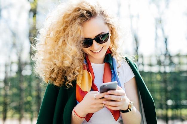 Mulher bonita com cabelo encaracolado, usando óculos escuros e jaqueta verde, segurando o smartphone nas mãos
