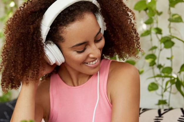 Mulher bonita com cabelo escuro crespo, usa fones de ouvido modernos brancos, escuta faixa de áudio, conectada a dispositivo irreconhecível. aluna feliz ouve músicas favoritas em casa, sendo melomana