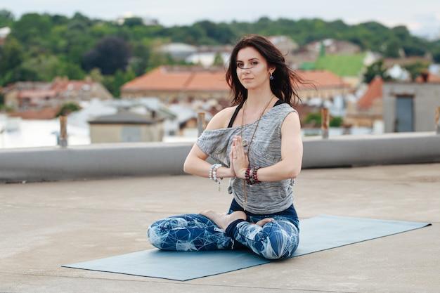 Mulher bonita com cabelo escuro praticando ioga no telhado