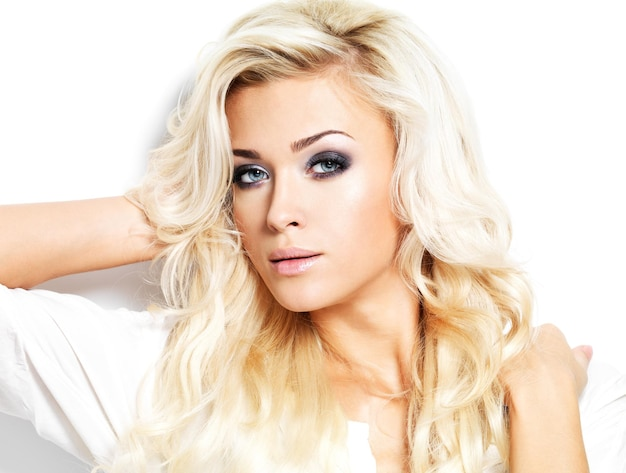 Mulher bonita com cabelo loiro comprido encaracolado. retrato de modelo com maquiagem brilhante. isolado no branco