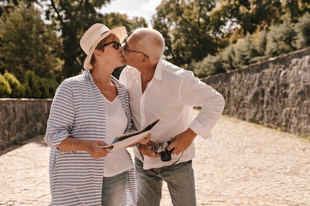 Mulher bonita com cabelo loiro de camisa com chapéu e blusa longa listrada beijando com homem de cabelos grisalhos em camisa de manga longa branca com câmera ao ar livre.