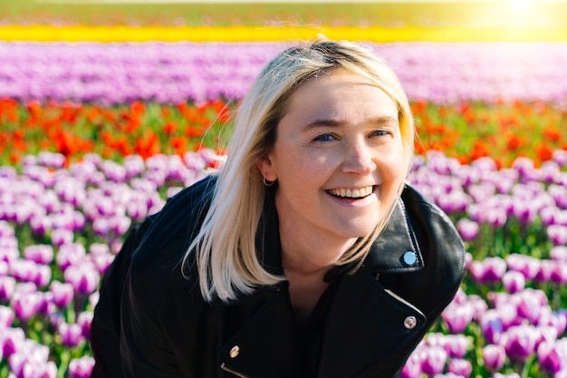 Mulher bonita com cabelo loiro em pé em campos de flores coloridas de tulipas na região de amsterdã
