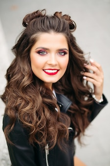 Mulher bonita com cabelo longo cacheado na jaqueta de couro.