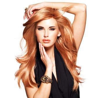 Mulher bonita com cabelo longo e liso vermelho em um vestido preto tocando seu rosto