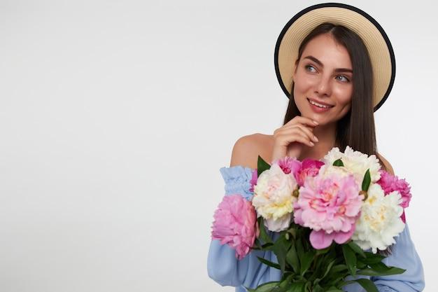 Mulher bonita com cabelo longo morena. usando chapéu e vestido azul. segurando um buquê de flores e tocando seu queixo, sonhando