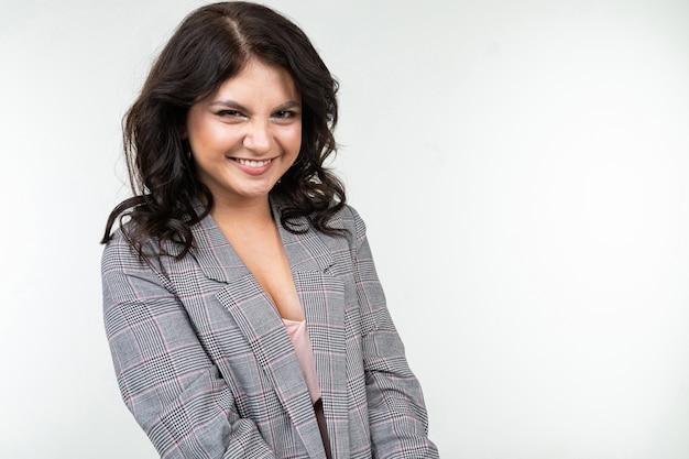 Mulher bonita com cabelo preto em uma jaqueta cinza quadriculada para escritório em um fundo branco com espaço de cópia