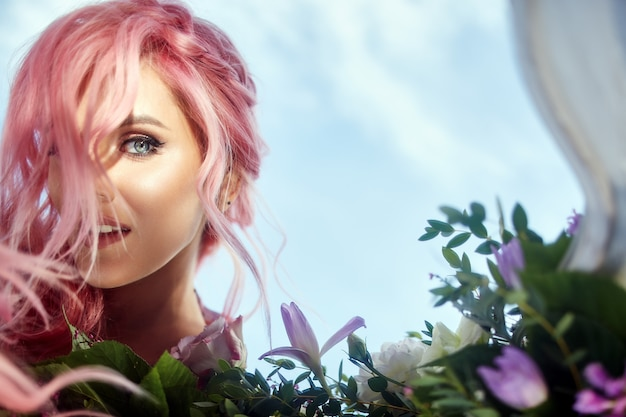 Mulher bonita com cabelo rosa segura grande buquê com vegetação e flores violetas