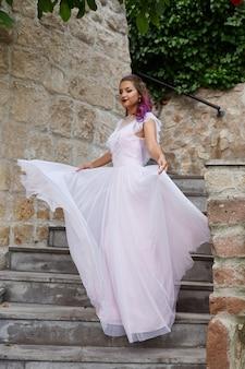 Mulher bonita com cabelo roxo em um vestido de noiva branco caminhando no jardim