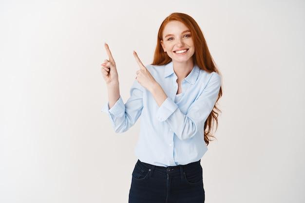 Mulher bonita com cabelo ruivo e pele clara, usando blusa de escritório e apontando para o canto superior esquerdo, mostrando o logotipo da empresa, parede branca