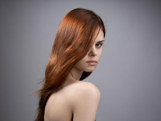 Mulher bonita com cabelo ruivo solto em um retrato de ombros descobertos de fundo cinza. foto de alta qualidade