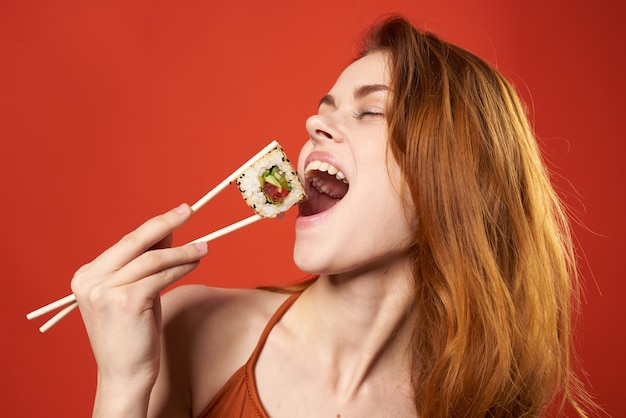 Mulher bonita com cabelo ruivo sushi pauzinhos dieta comida vermelho