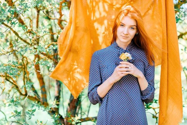 Mulher bonita com cabelo vermelho ao ar livre com véu laranja