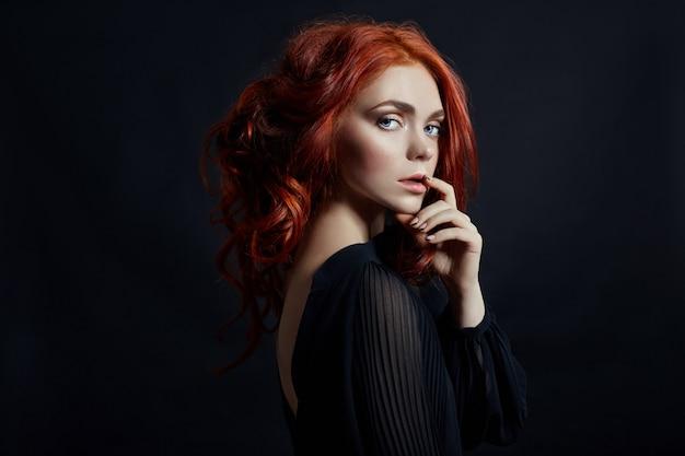 Mulher bonita com cabelo vermelho em uma parede preta. retrato de uma mulher de sucesso, pele pura, maquiagem natural, rosto de cuidados da pele. retrato de contraste de uma mulher adulta
