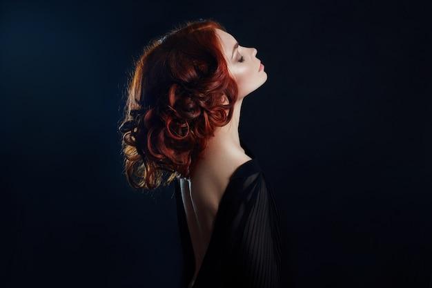 Mulher bonita com cabelo vermelho no preto
