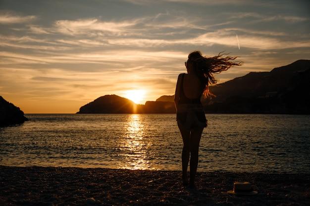 Mulher bonita com cabelos cacheados perto do mar