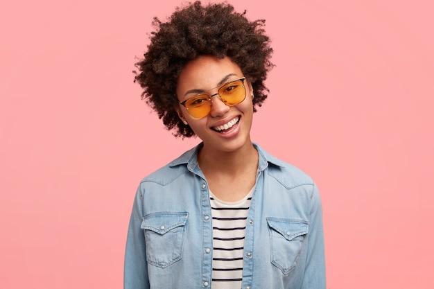 Mulher bonita com cabelos crespos, sorriso cheio de dentes, se sente bem depois de um dia de folga, feliz por receber um bom feedback