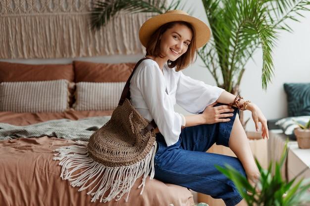 Mulher bonita com cabelos curtos relaxantes em seu quarto, estilo boho, palmeiras e macramê na parede