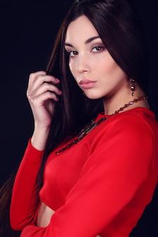 Mulher bonita com cabelos escuros e maquiagem de noite. jóias e beleza.