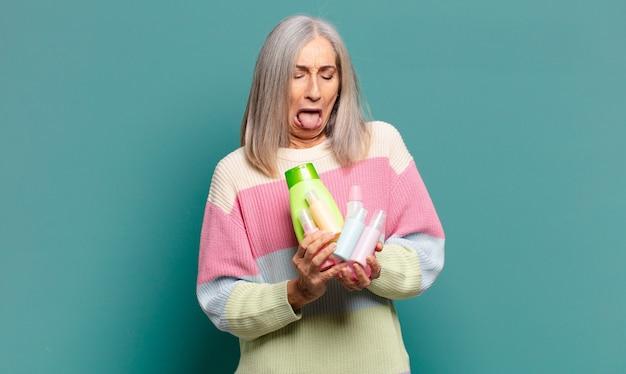 Mulher bonita com cabelos grisalhos e produtos para a pele