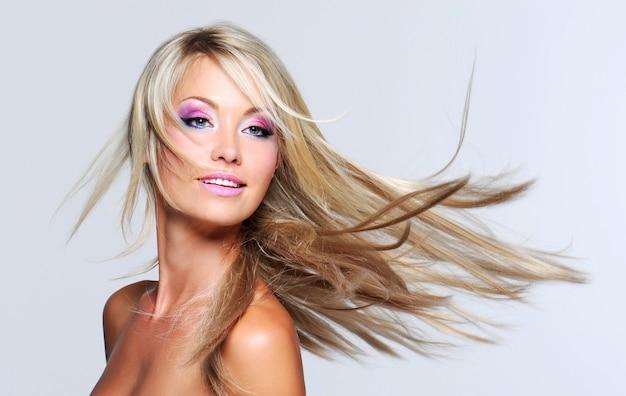 Mulher bonita com cabelos longos e lisos e maquiagem multicolorida