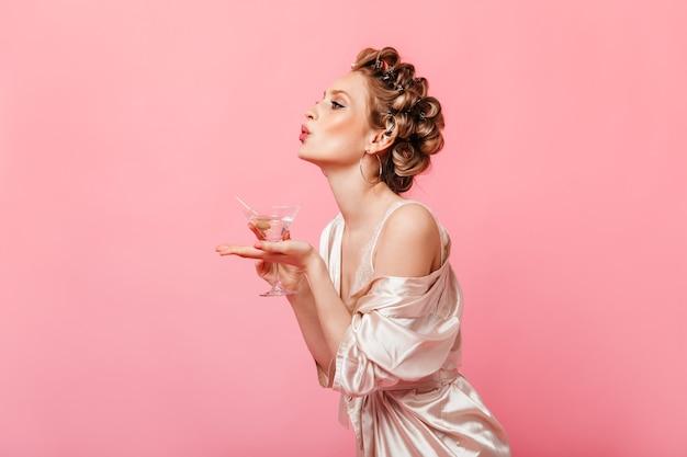 Mulher bonita com cabelos ondulados, vestida com um robe de seda, segurando uma taça de martini e mandando um beijo