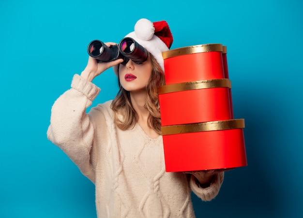 Mulher bonita com caixa de presente e binóculos